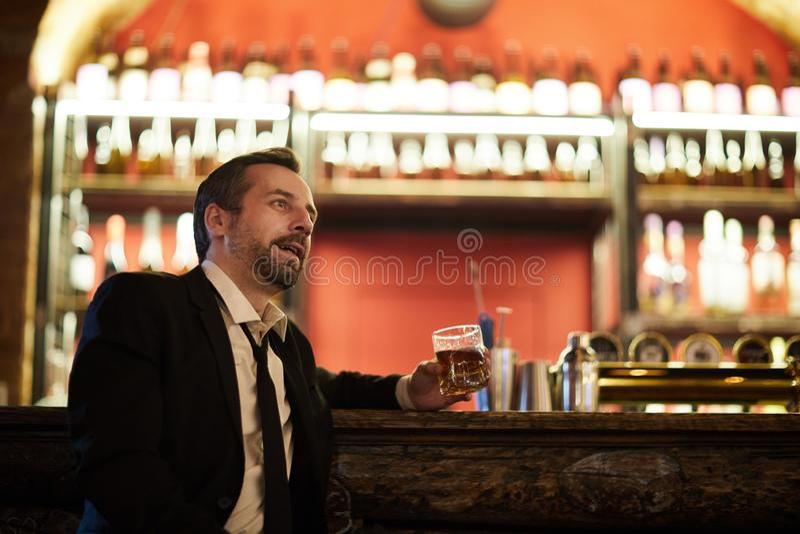 Uomo d'affari che si rilassa dal contatore di Antivari fotografia stock