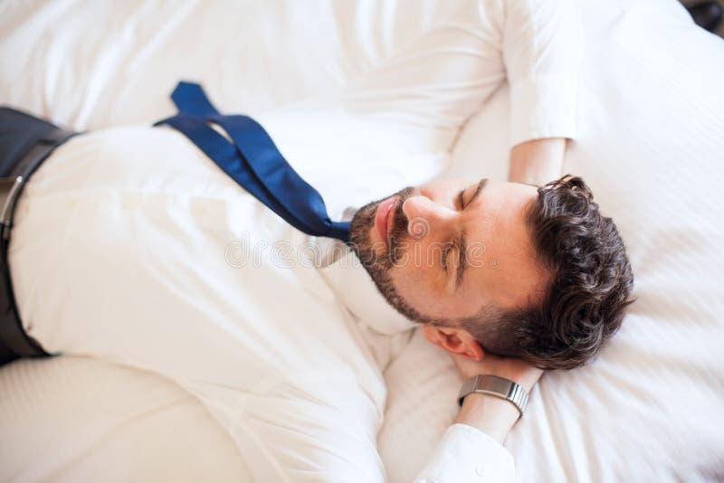 Uomo d'affari che si rilassa su un letto fotografia stock