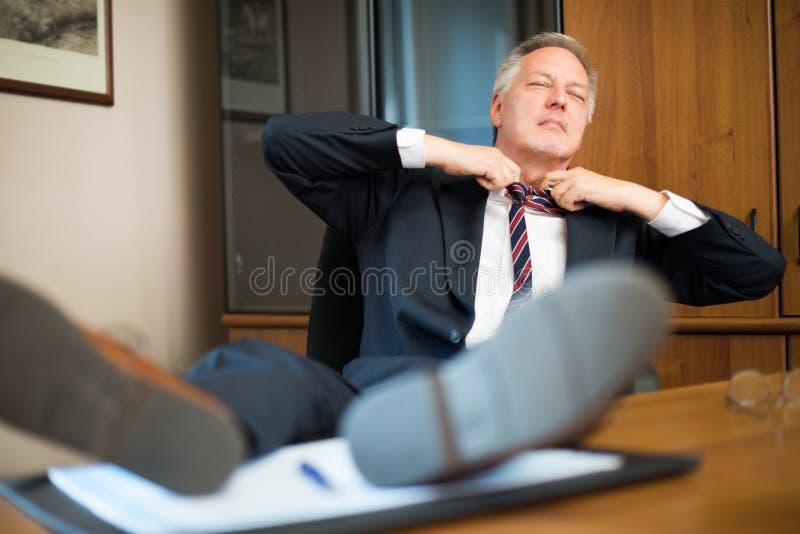 Uomo d'affari che si rilassa sulla sua sedia fotografie stock libere da diritti