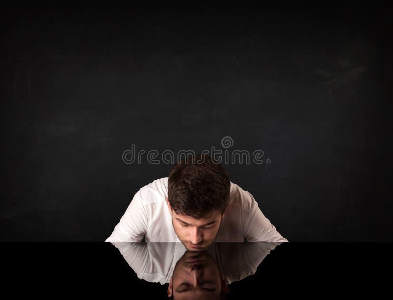Uomo d'affari che si siede ad uno scrittorio immagine stock libera da diritti