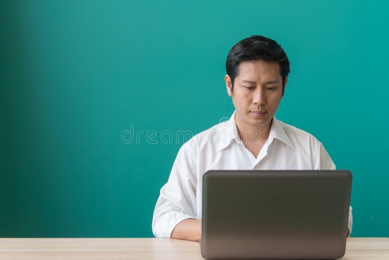 Uomo d'affari che si siede ad uno scrittorio facendo uso di un computer portatile fotografia stock libera da diritti