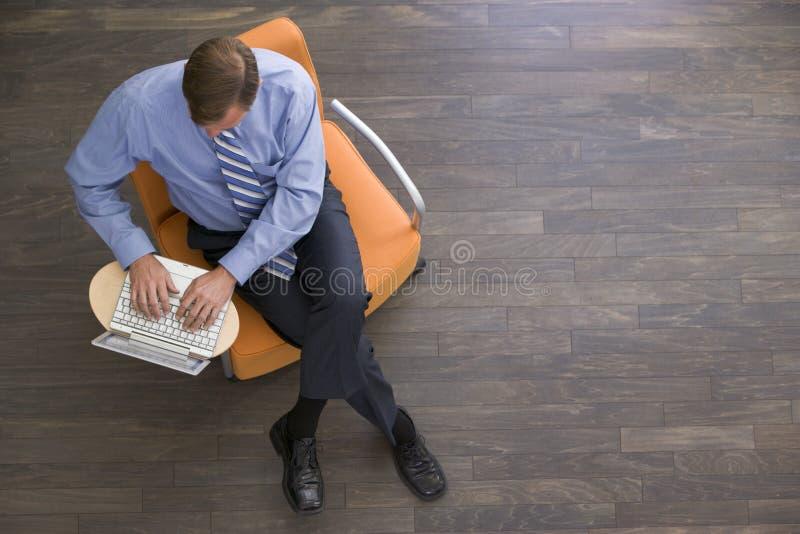 Uomo d'affari che si siede all'interno con il computer portatile fotografie stock