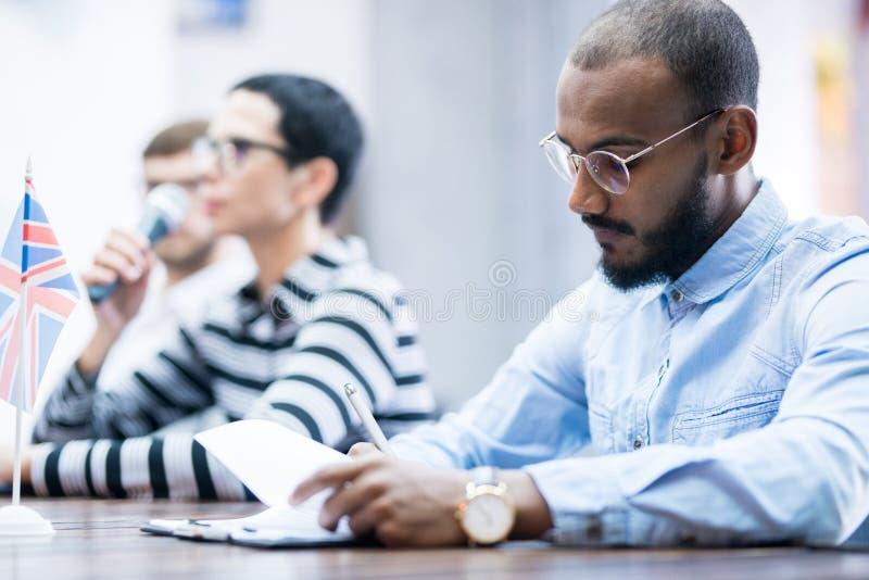Uomo d'affari che si siede alla conferenza fotografie stock