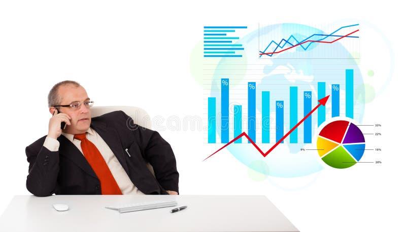 Uomo d'affari che si siede allo scrittorio con le statistiche e che fa un telefono c fotografia stock libera da diritti