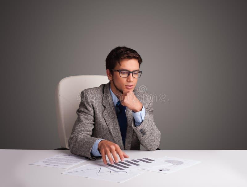 Uomo d'affari che si siede allo scrittorio e che fa lavoro di ufficio fotografie stock libere da diritti