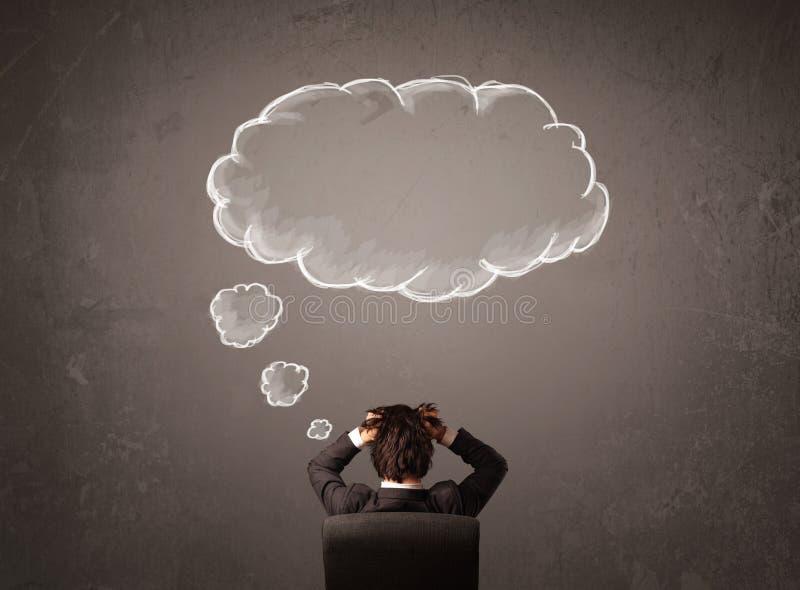 Uomo d'affari che si siede con il pensiero della nuvola sopra la sua testa fotografie stock