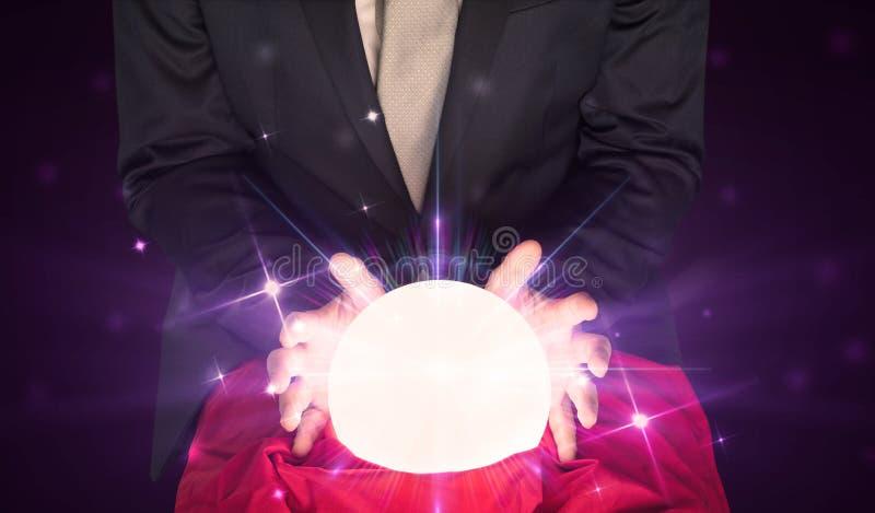 Uomo d'affari che si siede con la sfera di cristallo nell'azione fotografia stock