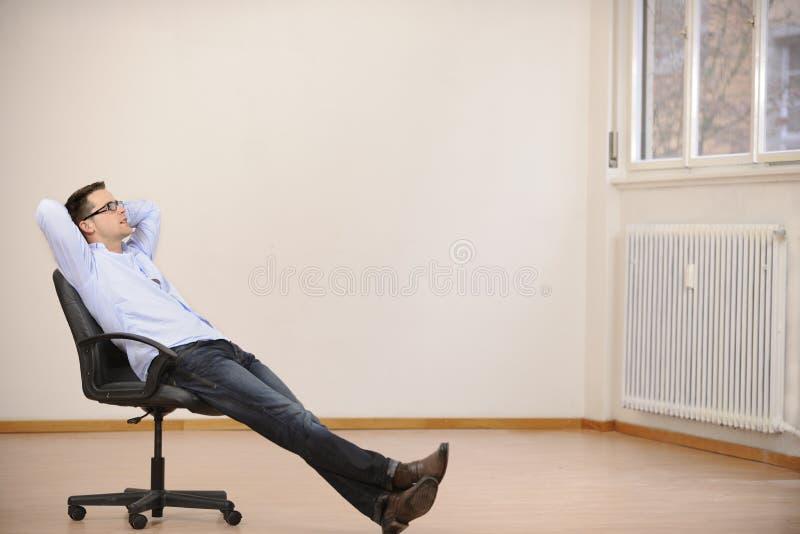 Uomo d'affari che si siede da solo nel nuovo nuovo ufficio fotografia stock libera da diritti