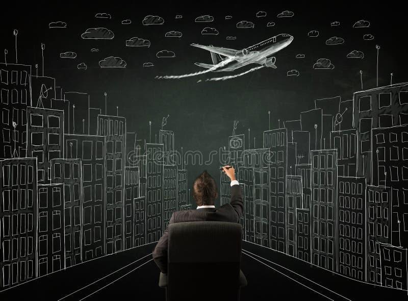 Uomo d'affari che si siede davanti ad un paesaggio urbano che attinge un chalkbo fotografie stock