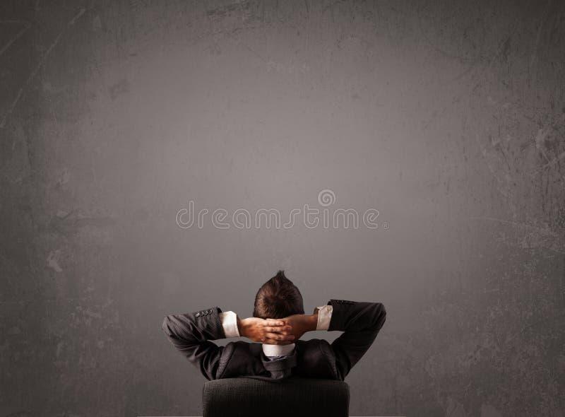 Uomo d'affari che si siede davanti ad una parete con lo spazio della copia fotografia stock
