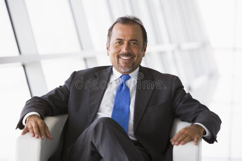 Uomo d'affari che si siede nell'ingresso dell'ufficio fotografia stock