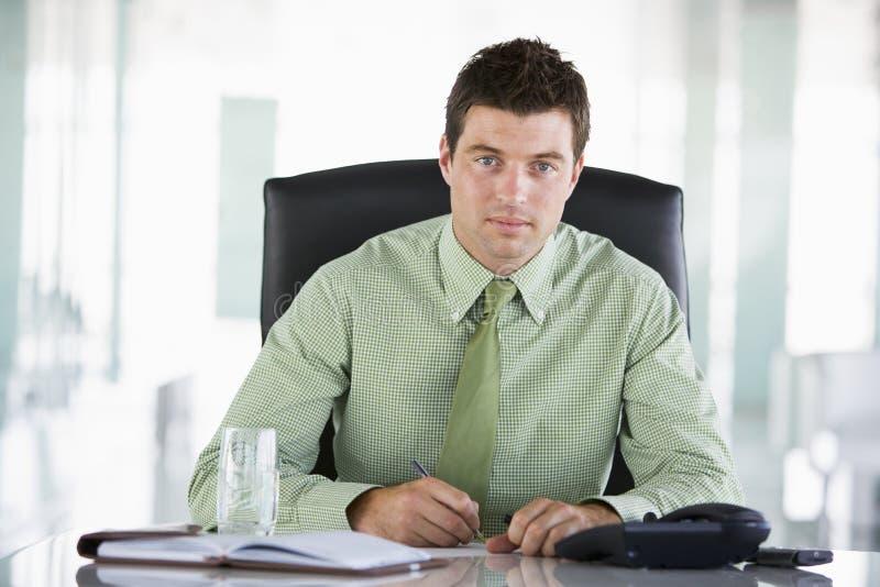 Uomo d'affari che si siede nell'ufficio fotografia stock libera da diritti