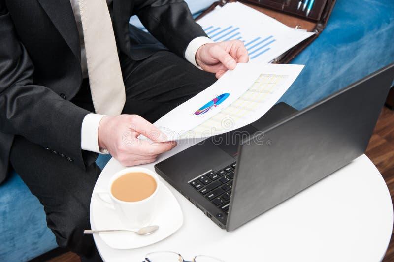 Uomo d'affari che si siede nell'ufficio dietro lo scrittorio e l'analisi di vendite controllata fotografie stock