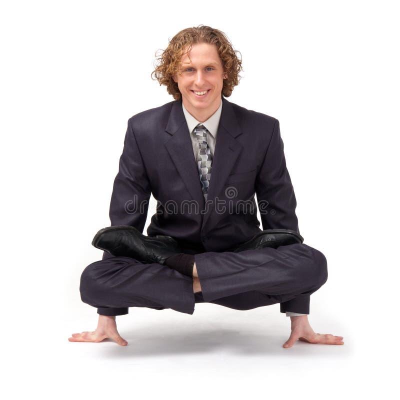 Uomo d'affari che si siede nella posizione di loto completa. immagini stock