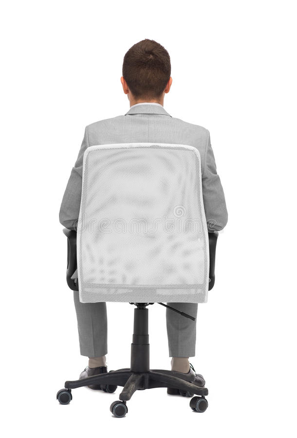 Uomo d'affari che si siede nella sedia dell'ufficio dalla parte posteriore fotografia stock libera da diritti