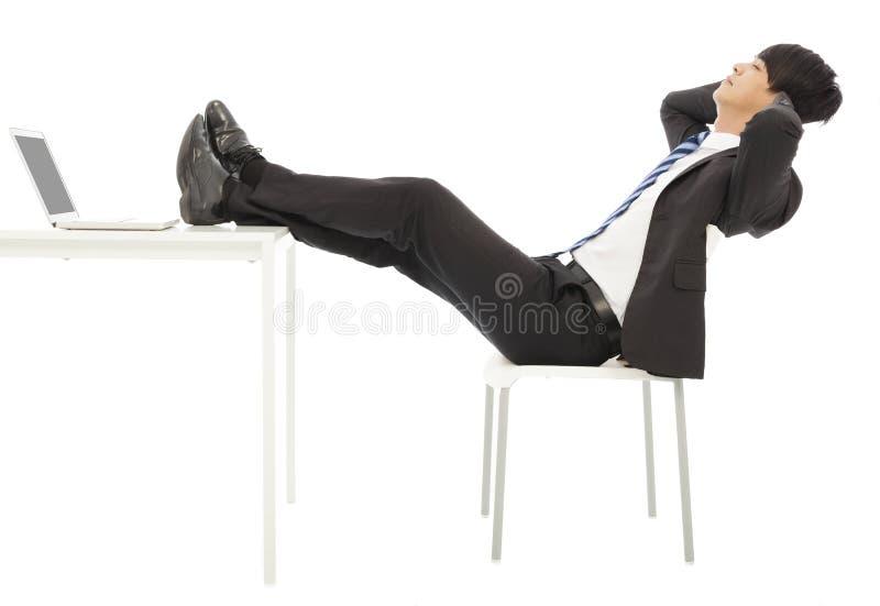 Uomo d'affari che si siede su una sedia per prendere un resto fotografia stock