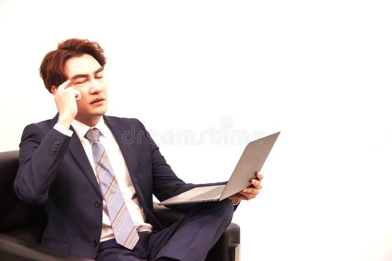 Uomo d'affari che si siede sul sofà nero, persona dura di pensiero che prende decisione economica su Internet dal computer portat immagini stock libere da diritti