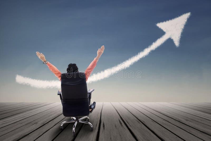 Uomo d'affari che si siede sulla sedia con i braccioli alzati ed il segno alto della freccia immagine stock