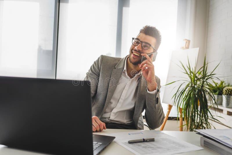 Uomo d'affari che si siede sulla sua scrivania che lavora ad un computer e che per mezzo dello Smart Phone fotografia stock libera da diritti