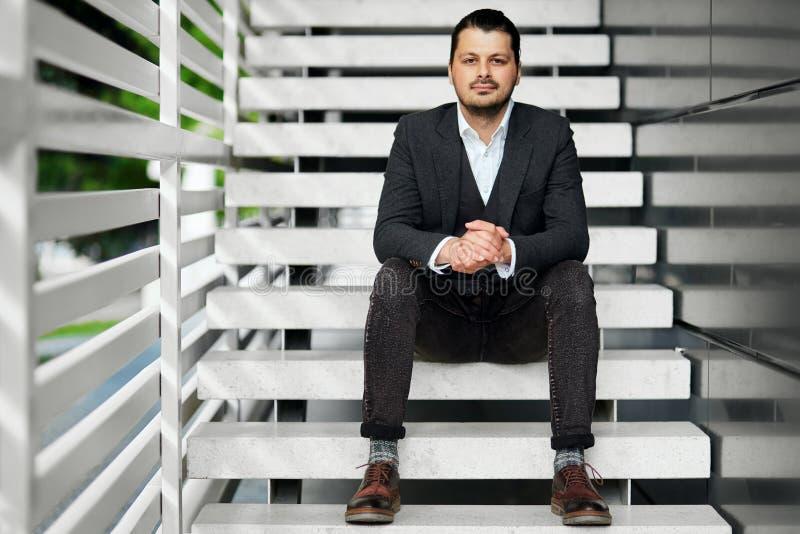 Uomo d'affari che si siede sulle scale fotografia stock