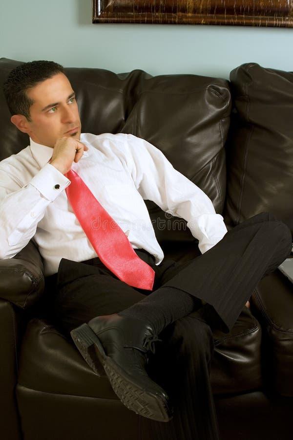 Uomo d'affari che si siede sullo strato immagini stock libere da diritti