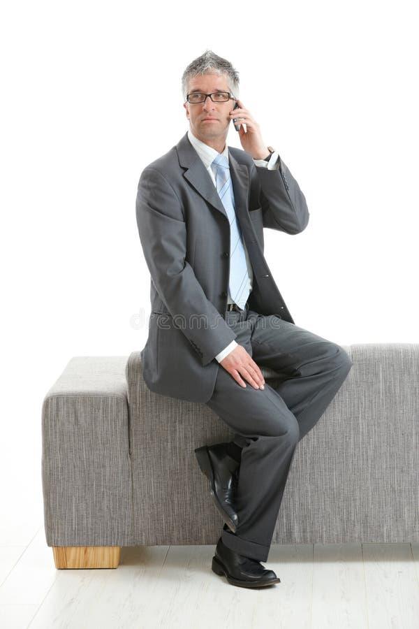 Uomo d'affari che si siede sullo strato che comunica sul telefono fotografia stock