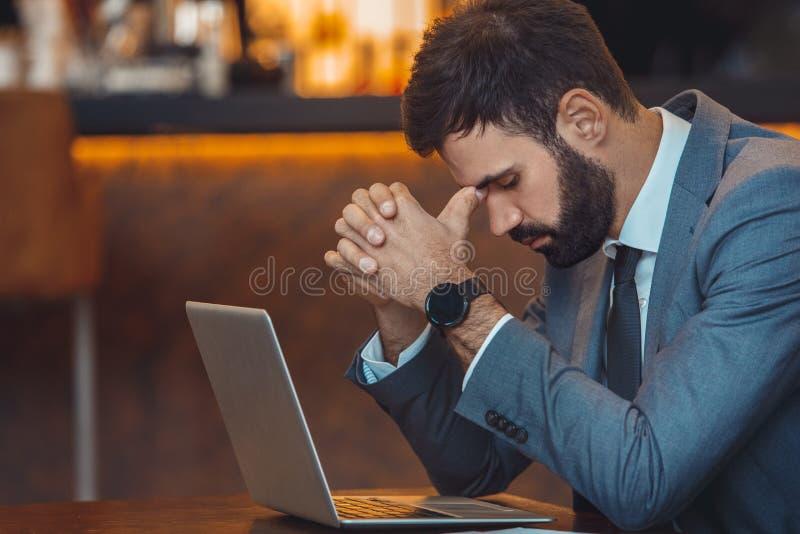 Uomo d'affari che si siede in un funzionamento della barra del centro di affari responsabile immagini stock libere da diritti