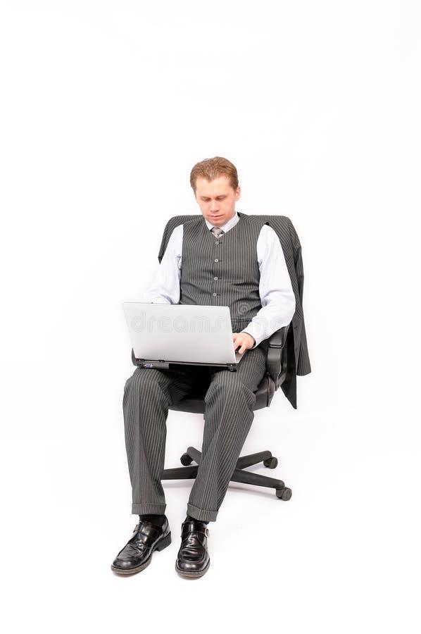 Uomo d'affari che si siede in una poltrona con un computer portatile. fotografia stock libera da diritti