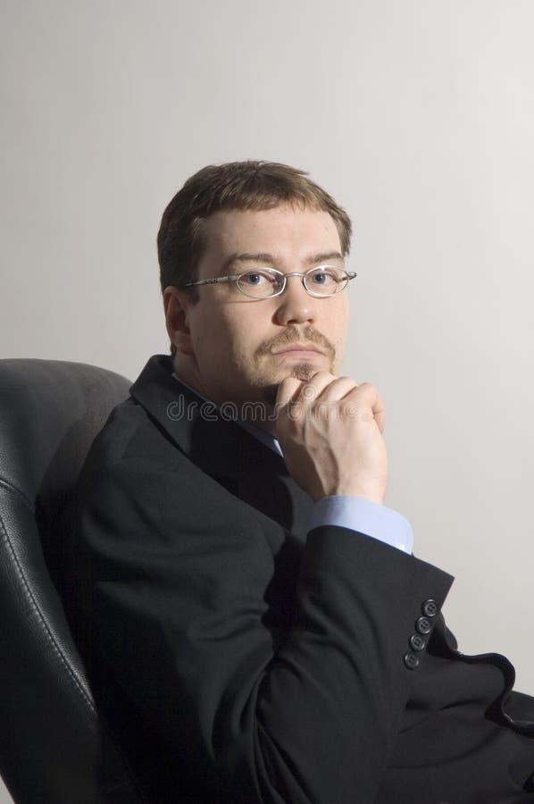 Uomo d'affari che si siede in una presidenza fotografia stock libera da diritti
