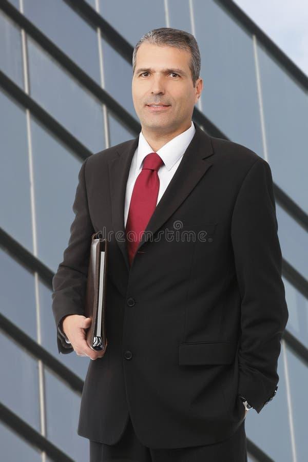 Uomo d'affari che smilling con il taccuino immagine stock
