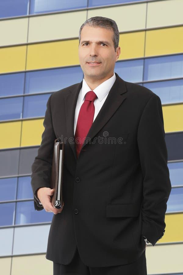 Uomo d'affari che smilling con il taccuino fotografia stock