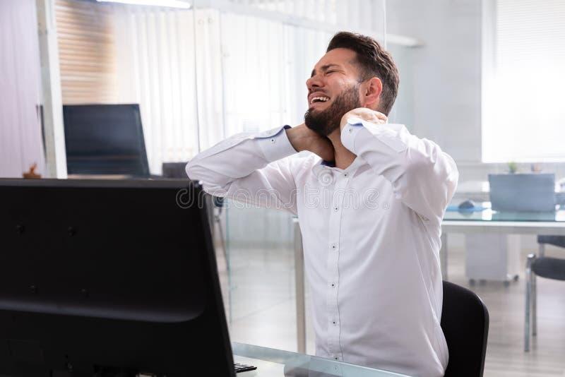 Uomo d'affari che soffre dal dolore al collo fotografia stock