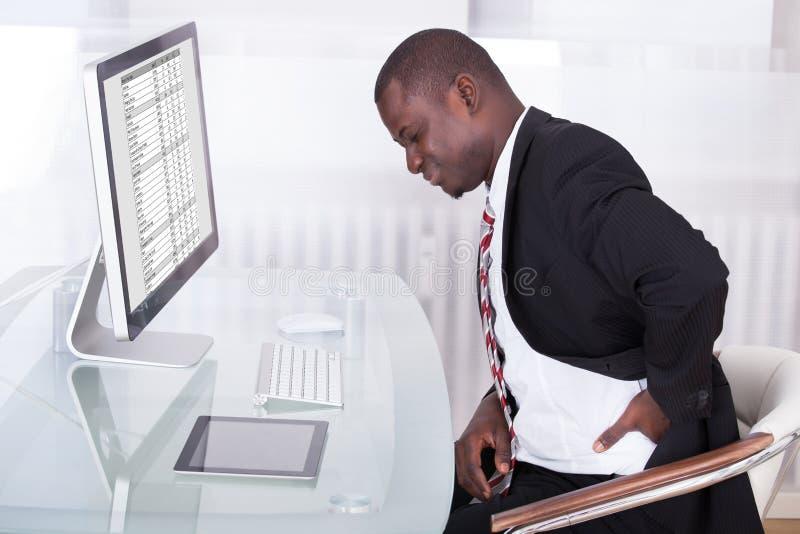 Uomo d'affari che soffre dal dolore alla schiena fotografie stock libere da diritti