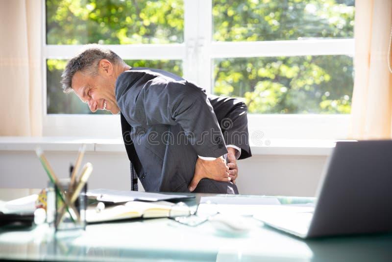 Uomo d'affari che soffre dal dolore alla schiena immagine stock