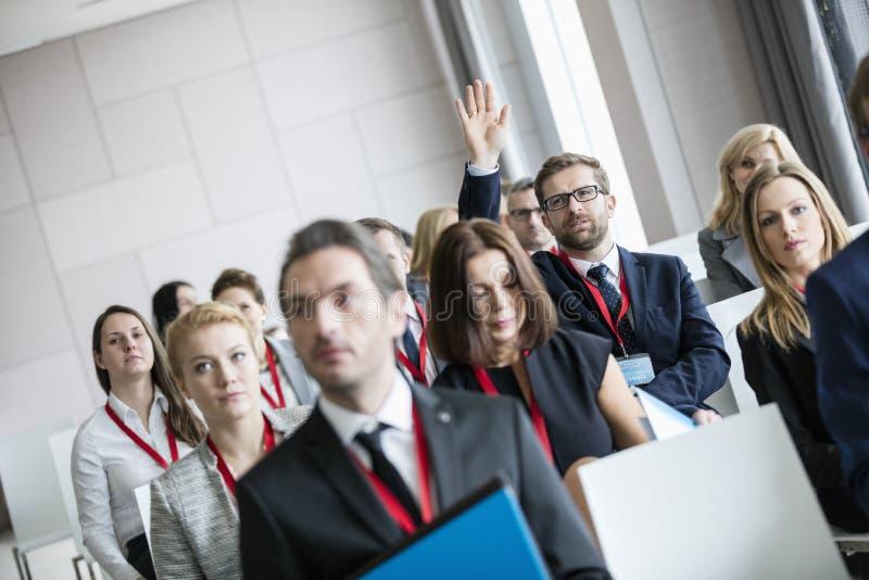 Uomo d'affari che solleva mano durante il seminario al centro di convenzione fotografia stock