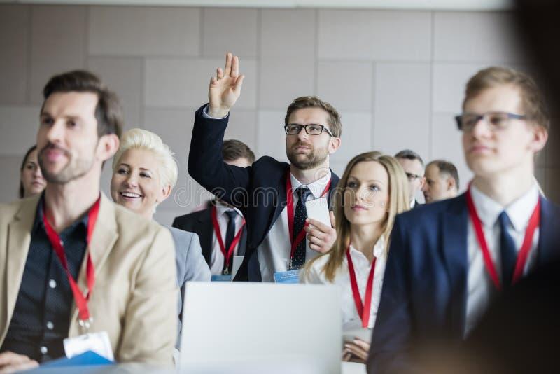 Uomo d'affari che solleva mano durante il seminario al centro di convenzione immagine stock libera da diritti