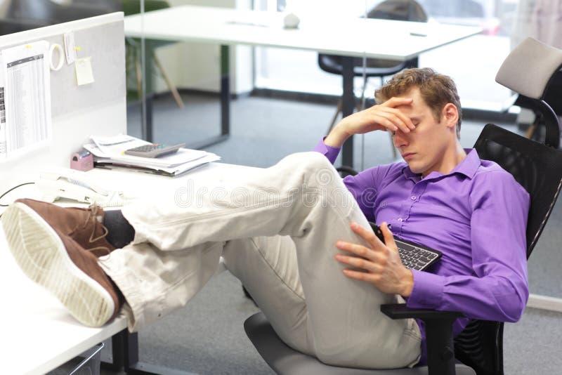 Uomo d'affari che sonnecchia sopra la sua compressa in ufficio immagine stock