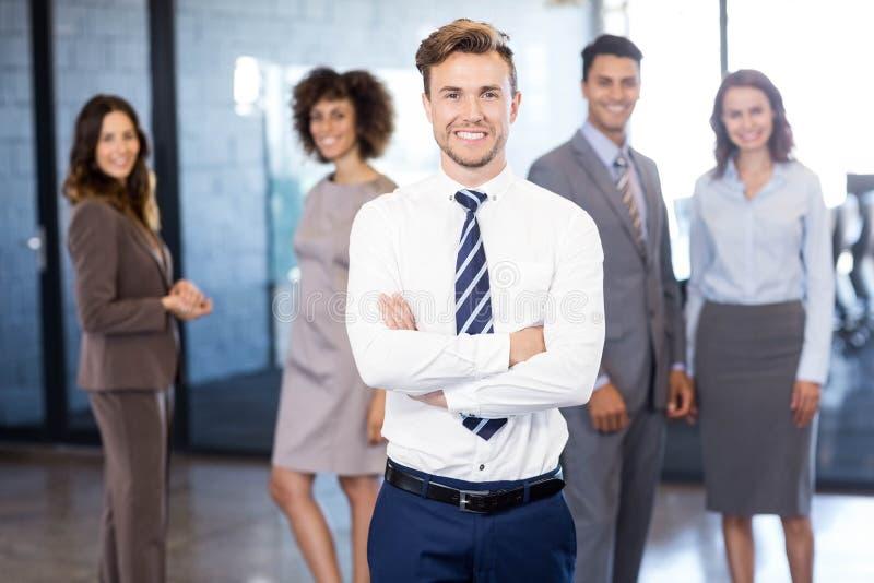 Uomo d'affari che sorride alla macchina fotografica mentre i suoi colleghi che posano nel fondo immagini stock libere da diritti