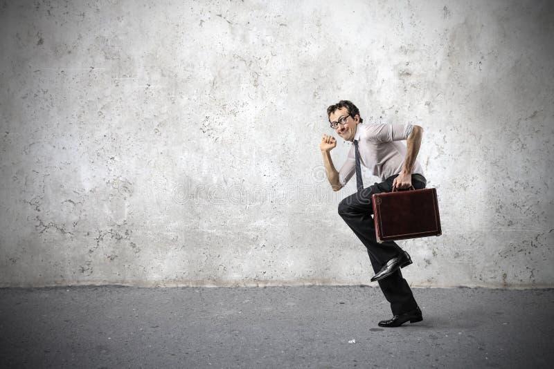 Uomo d'affari che sorride e che corre velocemente immagine stock