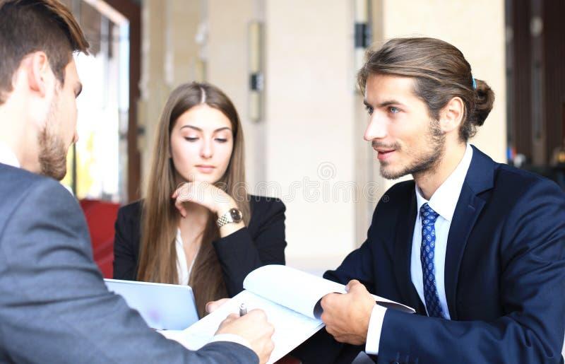 Uomo d'affari che sorride felicemente come suo socio commerciale infine che firma contratto importante fotografie stock