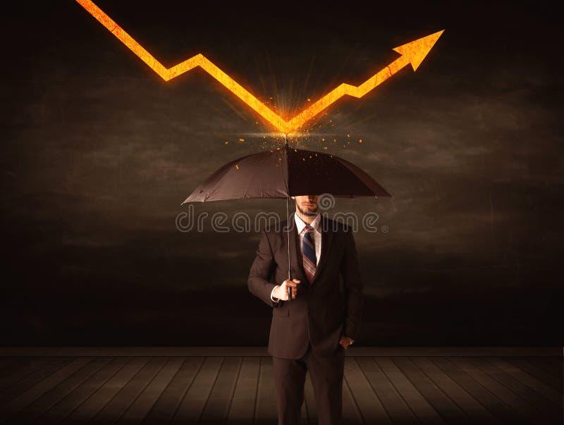 Uomo d'affari che sta con l'ombrello che tiene freccia arancio fotografia stock