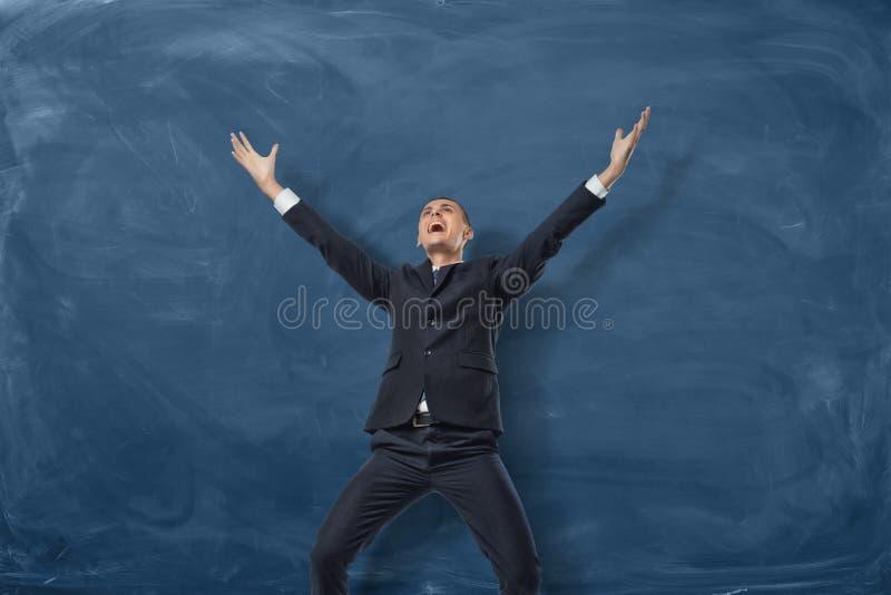 Uomo d'affari che sta con le armi stirate e che grida sui precedenti blu della lavagna fotografie stock