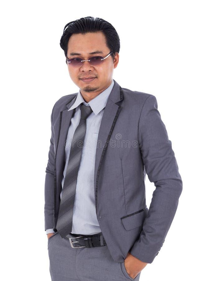 Uomo d'affari che sta con le mani in tasche isolate sul BAC bianco immagine stock libera da diritti