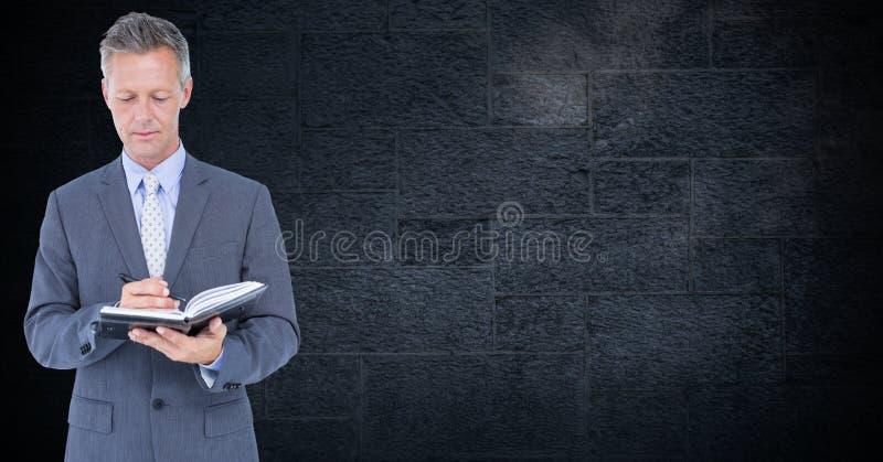 Uomo d'affari che sta contro la parete nera e che scrive sul diario immagine stock