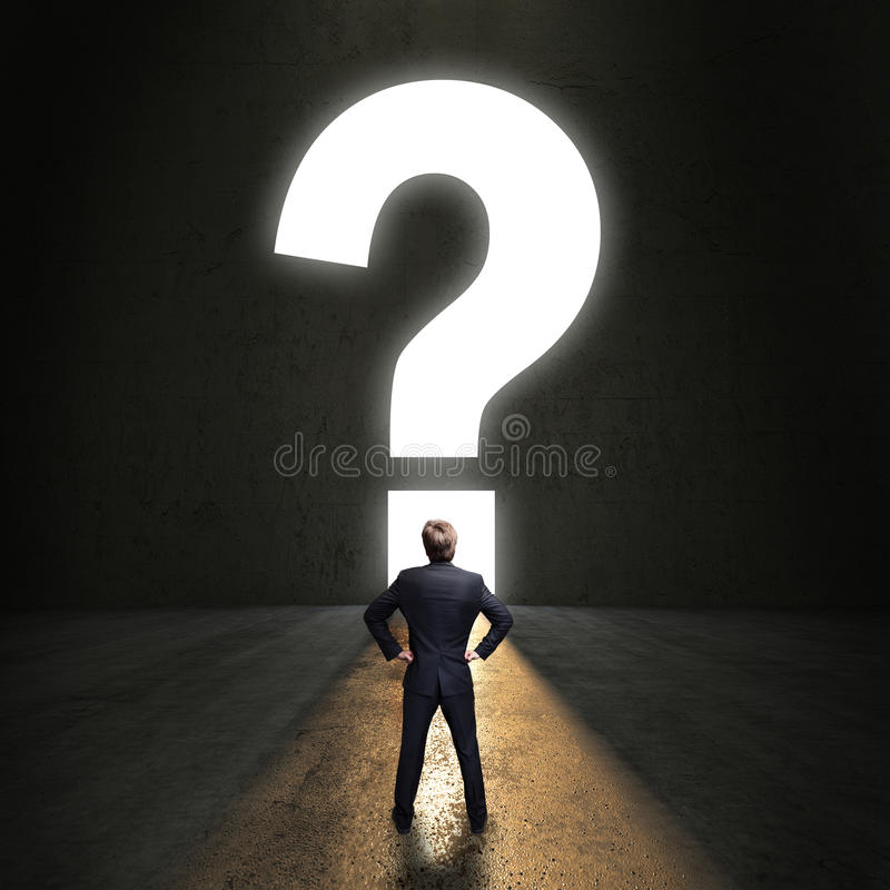 Uomo d'affari che sta davanti ad un portale del questionmark immagini stock libere da diritti