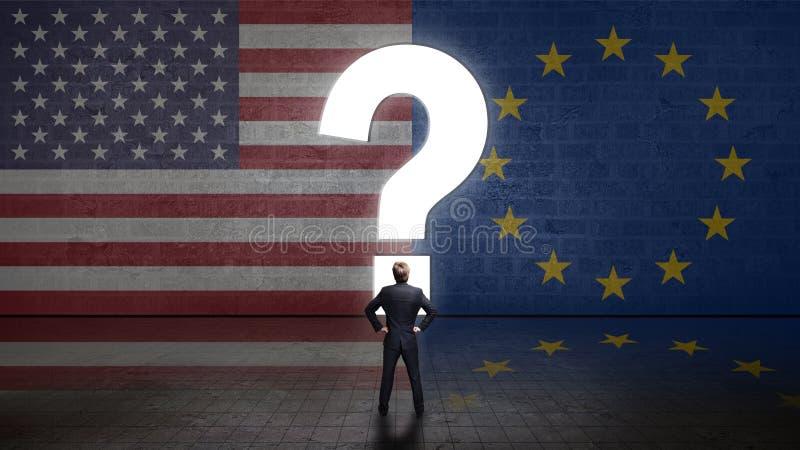 Uomo d'affari che sta davanti ad una parete con un questionmark ed alle bandiere degli S.U.A. e dell'Unione Europea fotografia stock