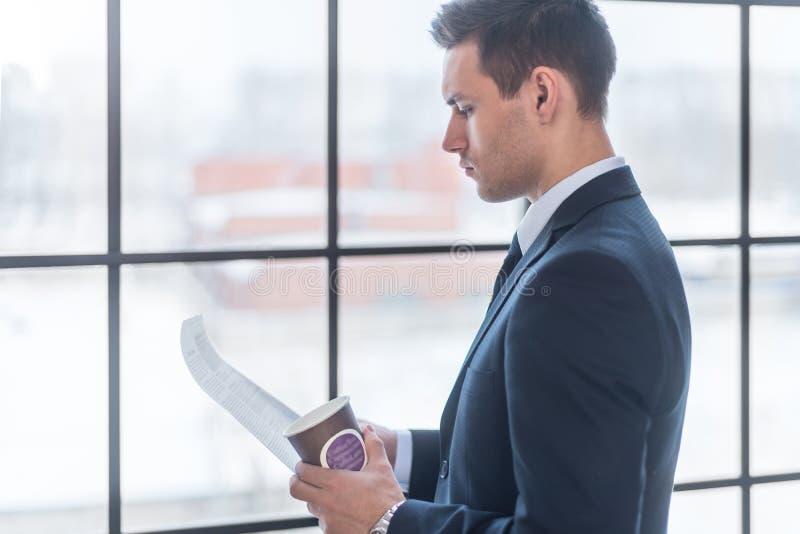 Uomo d'affari che sta in documenti della lettura dell'ufficio e caffè bevente immagine stock libera da diritti