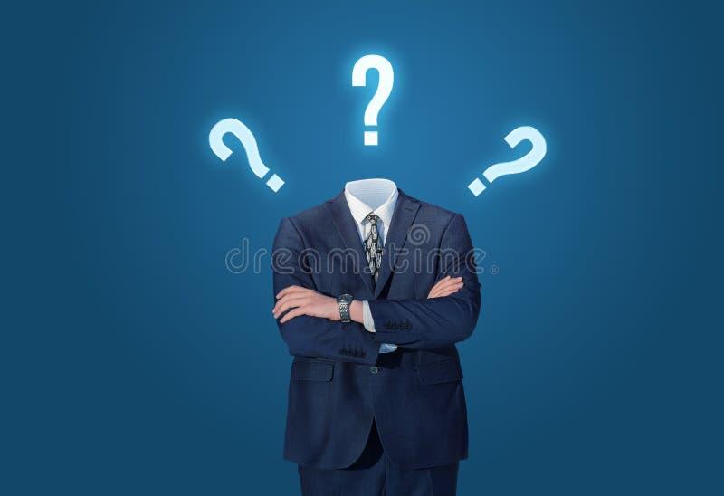 Uomo d'affari che sta senza testa con i punti interrogativi del disegno immagini stock