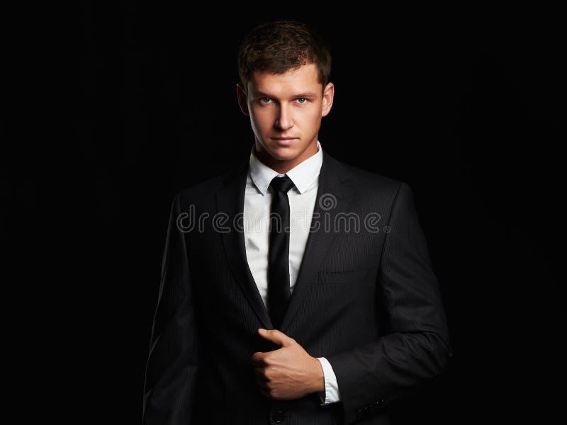 Uomo d'affari che sta sul fondo nero Giovane bello in vestito immagini stock libere da diritti