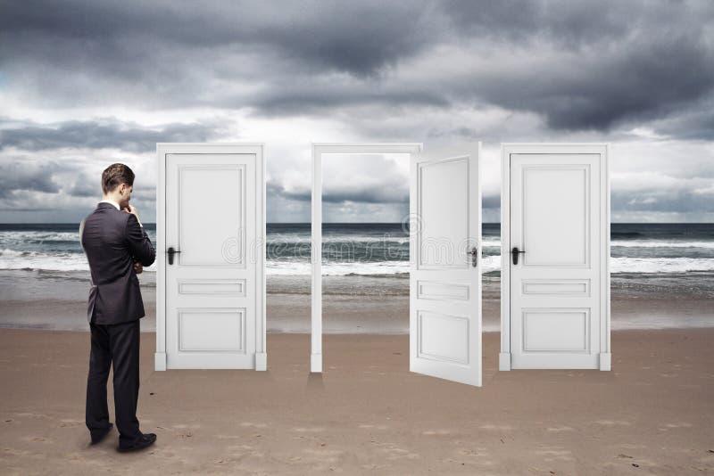 Uomo d'affari che sta sulla spiaggia fotografia stock libera da diritti